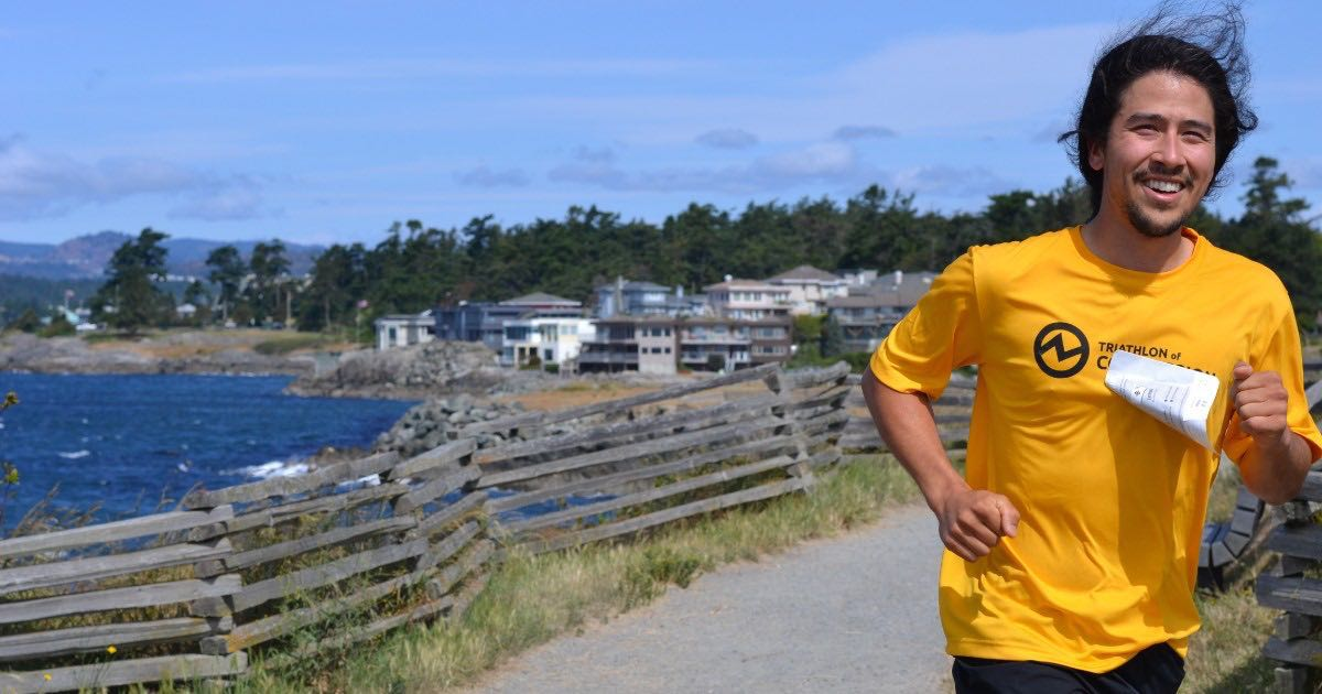 A man in a bright yellow shirt running and smiling is right of center. There is ocean in the background and his hair is blowing in the wind.