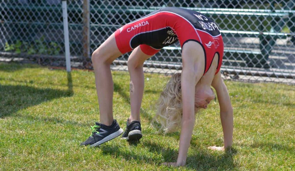 A young person in a red and black triathlon body suit doing a bridge on the grass.