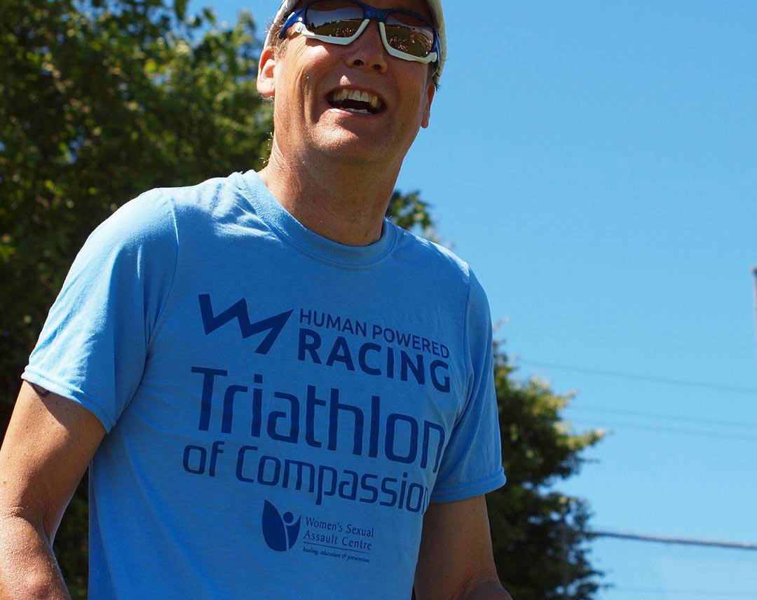 A participant of the Triathlon of Compassion has a big smile while wearing a race t-shirt.
