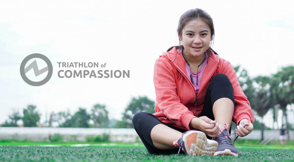 A young woman laces up her shoes in preparation for the Tri of Compassion.